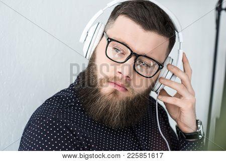 Portrait Of Pensive Bearded Man In Eyeglasses Listen Music In Headphones