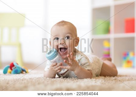 Cute Baby Boy Drinking From Bottle. Kid Lying On Carpet In Nursery At Home. Smiling Child Is 7 Month