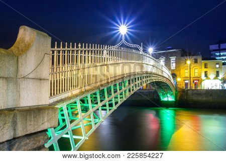 DUBLIN, IRELAND - FEBRUARY 20, 2012: The ha'penny bridge in Dublin at night, Ireland. Dublin is the capital and largest city of Ireland. Located on the east coast, at the mouth of the River Liffey.