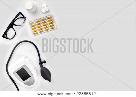 Electronic Medical Tonometer For Measuring Blood Pressure, Tablets In Capsules And Glasses On A Whit