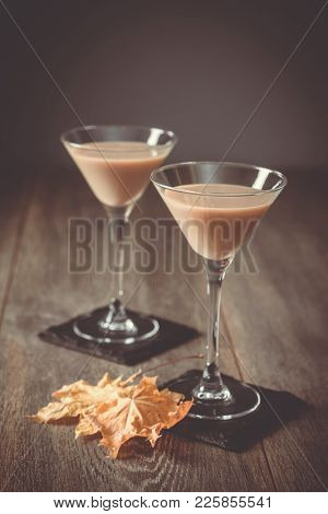 Two Irish cream liqueurs on slate coasters with autumn leaves