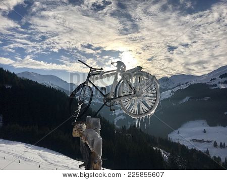Alpine Landscape With Frozen Bicycle On A Signpost With Great Cloudscape
