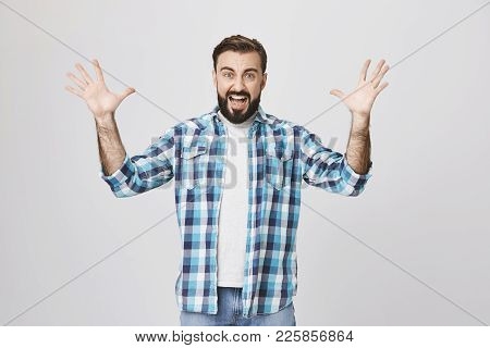 Portrait Of Angry Insane European Man, Shouting And Spreading His Hands While Gesturing, Over Gray B