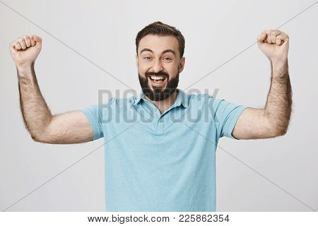 Happy Bearded Man Raising His Hands Showing Victory Gesture Near White Wall. Handsome Guy Just Won I