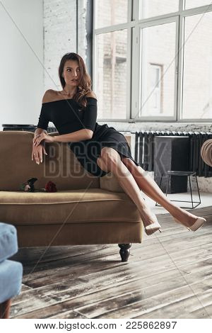 Simply Stunning. Attractive Young Woman In Elegant Black Dress Keeping Legs Crossed At Knee And Look
