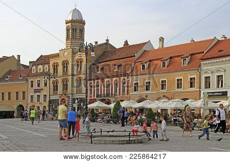 Brasov, Romania - July 25, 2017: People Are Walking By Council Square In Brasov, Romania