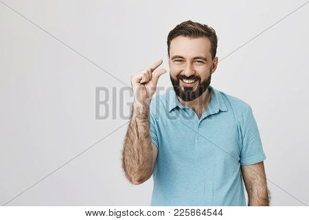 Beautiful Man Showing Small Thing While Smiling And Standing Near White Wall. Handsome Bearded Perso