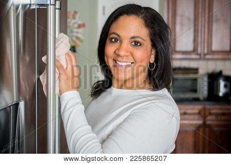 Happy hispanic mom cleaning her new refrigerator