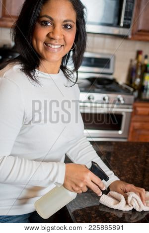 Hispanic woman cleaning her kitchen counter with a cloth