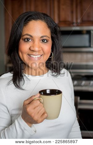 Happy hispanic woman drinking coffee in the kitchen