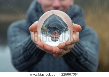 Closeup Of Man In Front Of Lake Holding A Glass Ball