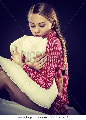 Adolescence Problems Concept. Sad Young Teenager Woman Sitting On Bed Feeling Depressed Hugging Pill