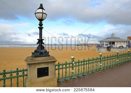 The Margate Seafront With A Designed Street Lamp In The Foreground And Margate Harbor Arm In The Bac