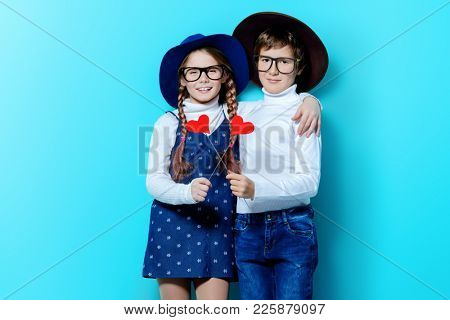 Happy pre-teen boy and girl holding two little hearts over blue background. Friendship. First love. Valentine's Day.