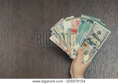 Female Hand With Money Of South-east Asia And American Hundred Dollar Bill. Currency Of Hong Kong, I