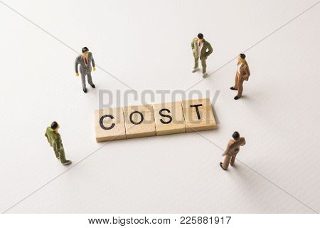 Miniature Figures Businessman : Meeting On Cost Word By Wooden Block Letters On White Paper Backgrou