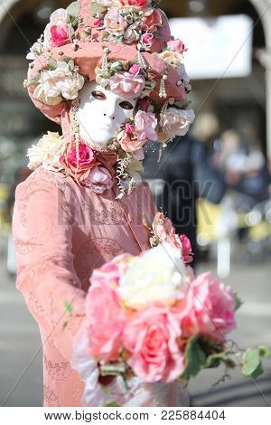 Venice, Italy - February 5, 2018: Person In Costume With Carnival Mask And A Big Bouquet Of Rose Flo