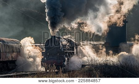 Steam Train Locomotive Approaching A Station Passing Through A Goods Yard Letting Of Smoke And Steam