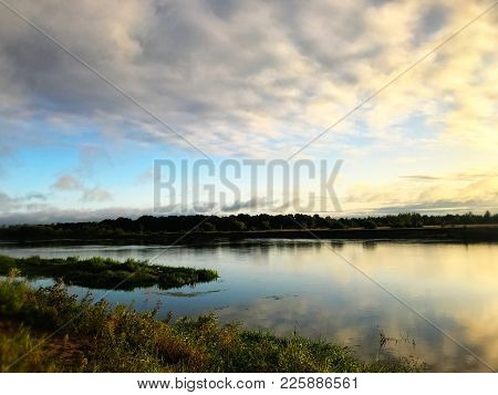 Forest River Landscape In The Morning. Green Trees, Thick Green Grass. Blue Sky And Calm Surface Of
