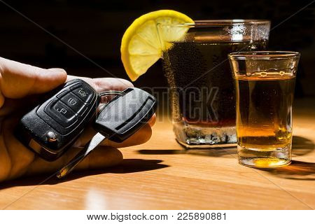A Man's Hand Holding Car Keys At A Bar