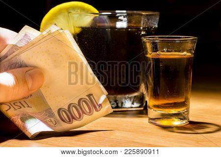 A Man's Hand Holding Banknotes At A Bar