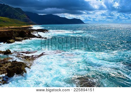 Waves Crashing Onto A Rocky Coastline At Tide Pools With Mountains Beyond Taken On A Rural Rugged Be