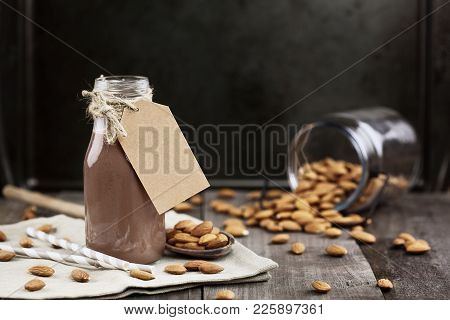 Organic Chocolate Almond Milk With Tag In A Glass Bottle With Whole Almonds Spilled Over A Rustic Wo