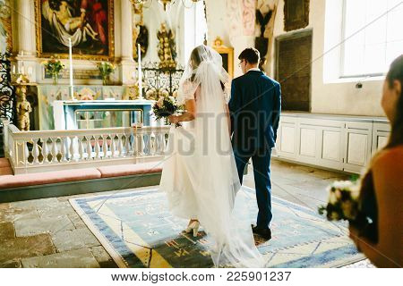 Bride And Groom In The Church During The Catholic Wedding Ceremony. Artwork