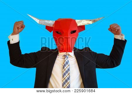 Businessman With Bull Mask And Blue Background Flexing His Muscles