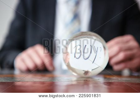 Closeup Of Man Holding Paper With Word Buy In Front Of Glass Ball
