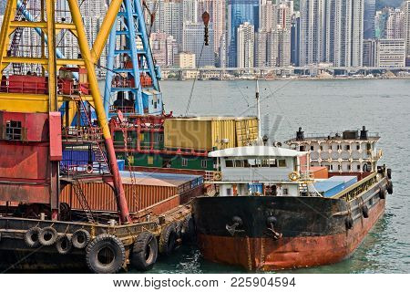 Stock Photo Of Unloading Shipping Containers From A Lighter In Victoria Harbour, Hong Kong.