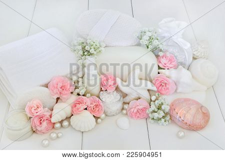 Spa and bathroom beauty treatment products with pink carnation and gypsophila flowers, ex foliating salt, shell soaps, body lotion, sponges, wash cloths, seashells and decorative pearls on white wood