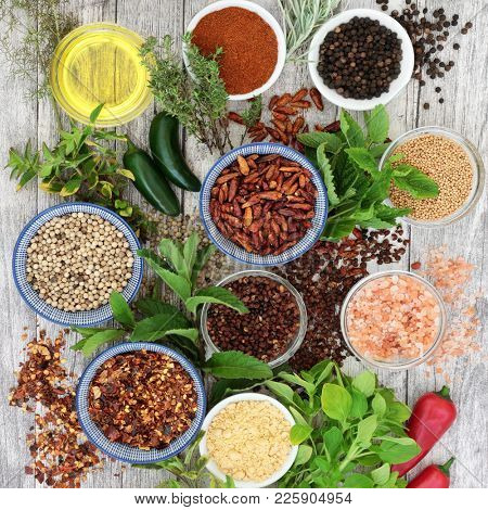 Herb and spice seasoning with fresh herbs and hot pepper spices selection with olive oil on rustic wood background. Top view.