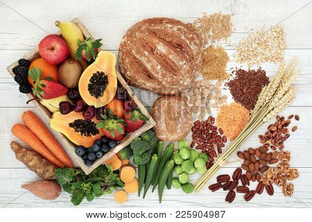 Healthy high fibre diet food concept with legumes, fruit, vegetables, wholegrain bread, cereals, grains, nuts and seeds. Super foods high in antioxidants, anthocyanins, omega 3 and vitamins. Top view.