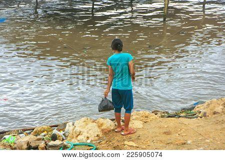 Local Woman Throwing Garbage In The Sea In Labuan Bajo Town, Flores Island, Nusa Tenggara, Indonesia
