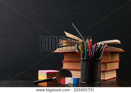 School Equipment On Black Desk, Close-up. Books On The Desk In The Auditorium With Blackboard On Bac