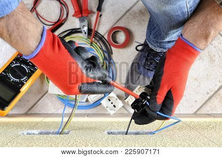 Electrician Technician At Work Blocks The Cable Between The Clamps Of A Socket In A Residential Elec