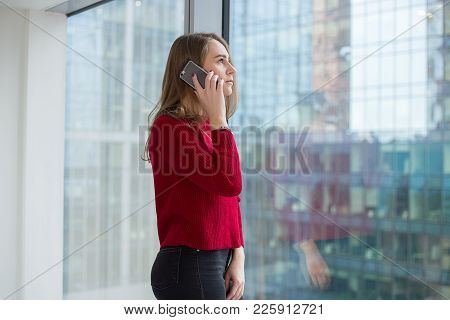 Business Woman At The Window Shows A Finger And Talks On The Phone. Telephone Negotiations And Appro