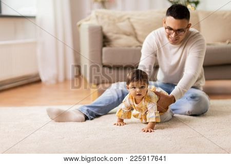 family, fatherhood and people concept - happy father with little baby daughter at home