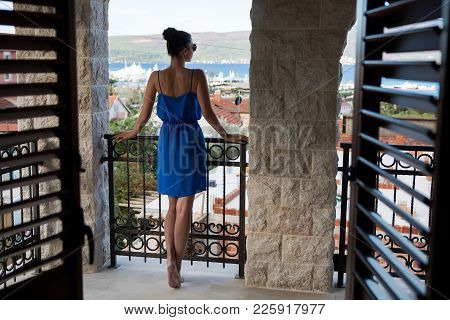 Girl In The Blue Dress Stands In The Doorway With Blinds