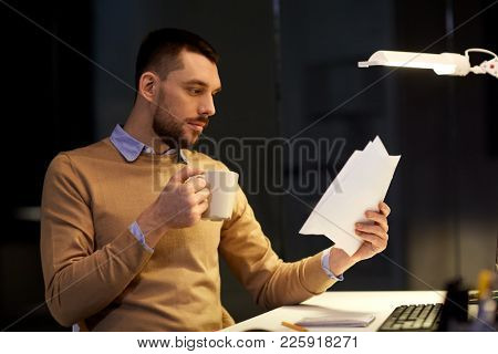 business, deadline and technology concept - man with papers working and drinking coffee at night office