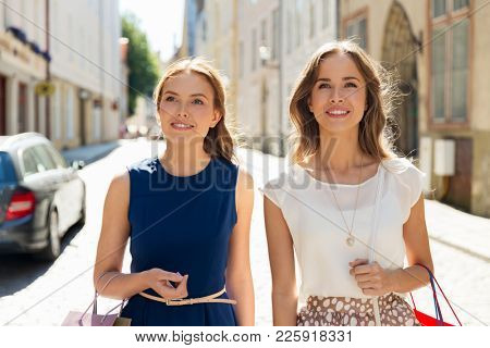 sale, consumerism and people concept - happy young women with shopping bags on city street