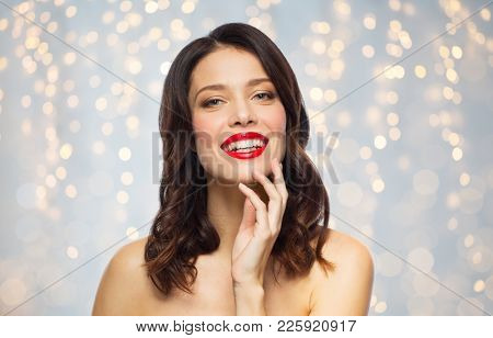 beauty, make up and people concept - happy smiling young woman with red lipstick posing over holidays lights background
