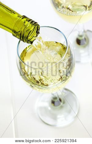 Glass Of White Wine Being Poured - White Wine Being Poured Into A Glass, Looking Down. Semi Sparklin
