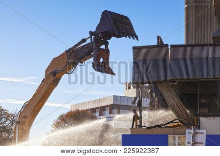 Demolition Or Deconstruction - An Excavator Just About To Take A Large Chunk Out Of A Building In Ch