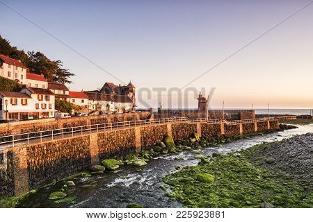 The River Lyn Passes The Harbour Wall On Its Way To The Sea At Lynmouth, Devon, England, Uk. Seen At