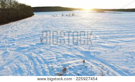Aerial View On Man Walking In Taiga Or Snow Field. Siberia, Endless Taiga. A Man Skiing Wanders Thro