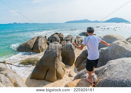 Boyrun And Play Amongst Large Rocks On Shore On Tropical Island Ko Samui, Thailand.