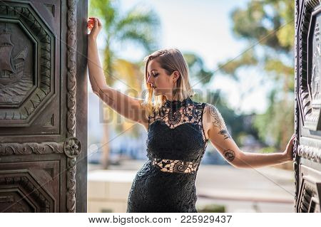 Backlit Blonde Woman In Black Lace Dress Opening Doors To Reveal The City.