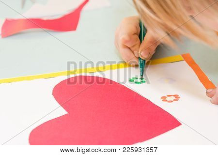 Child Draw A Postcard. Children Are Engaged In Needlework. The Girl Signs A Postcard On 14 February.